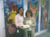 Ailbhe Ni Mhurchu, Business Process Analyst at Northern Trust presenting a donation to Majella Foley-Friel for ADAPT.